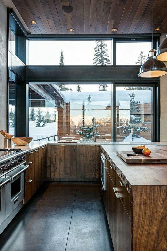 Cuisine ouverte sur l'extérieur grâce à ses fenêtres et à son mobilier en matériaux nobles